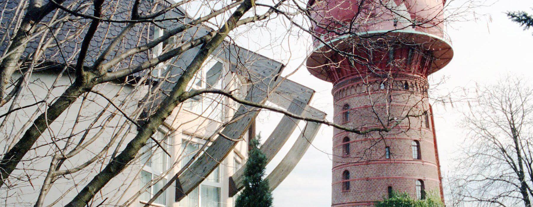 Außenaufnahme Haus und Turm hinter Baumzweigen